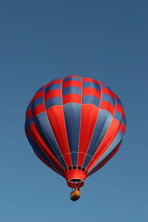 inflation basket: globo rojo y azul del aire caliente contra un cielo azul claro Foto de archivo