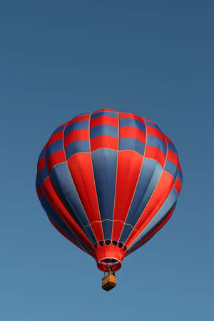 cody: red and blue hot air balloon against a clear blue sky