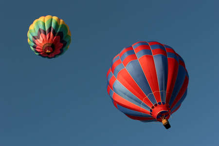two hot air balloons racing towards the sky photo
