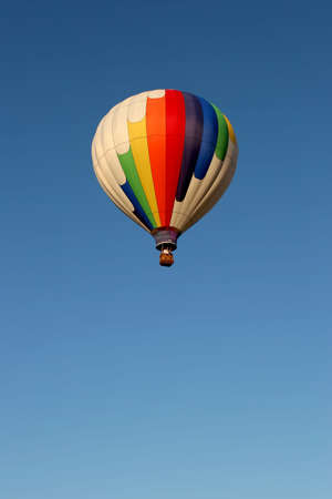 hot air balloon in flight, white balloon with rainbow colors against clear blue sky photo