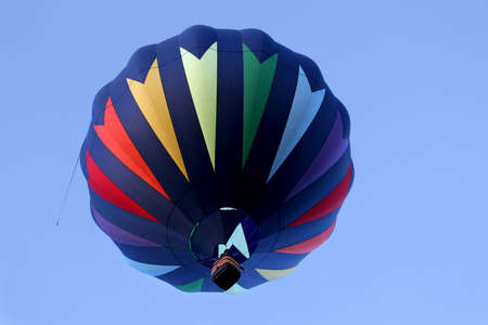 cody: hot air balloon in rainbow colors from below, against a blue sky. passenger pointing to the distance.wild west balloon fest, cody, wyoming Stock Photo