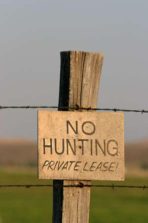 no hunting sign on wooden post with barbed wire photo