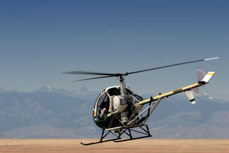 on the skids: a police  sheriff helicopter flying low over a field