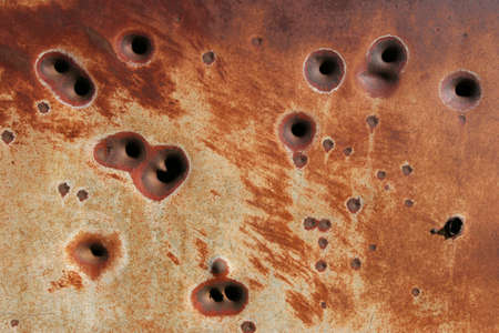 rusting: background - side of a rusting metal fridge with bullet holes Stock Photo