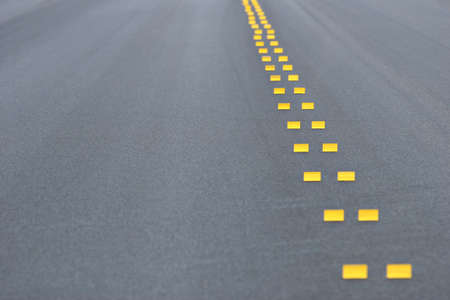 markings: road construction - abstract background with temporary yellow markings on asphalt. shallow depth of field with focus on a pair of markings. Stock Photo
