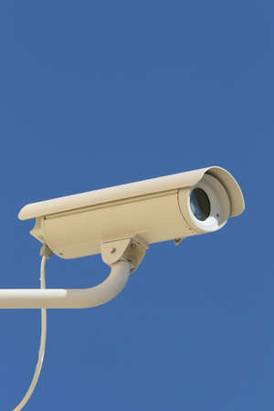 close circuit camera: security  surveillance camera against a clear blue sky