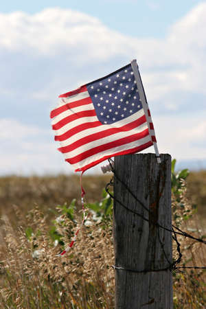 american midwest: american flag, battered and torn, flies proud on a fence post in the midwestern countryside