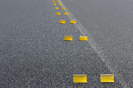 temporary: road work - abstract background with temporary yellow markings on fresh pavement. shallow depth of field with focus on first pair of markers.