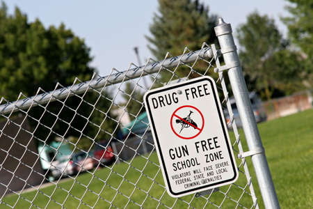 zone: drug and gun free school zone sign at a school yard. sign of the times.
