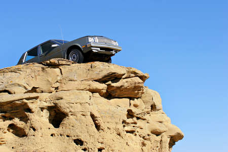 cliff edge: car dangerously close to the edge of a sandstone cliff