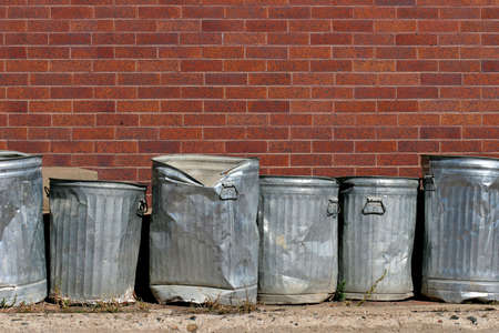 trash bin: line of metal trash cans against a red brick wall