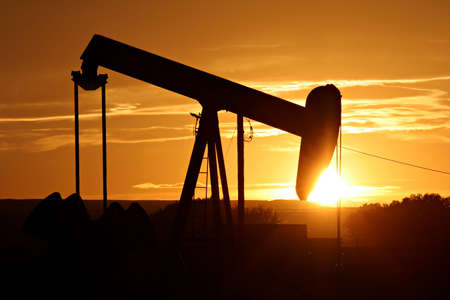 oilwell: oil pump silhouette against a bright orange sky Stock Photo