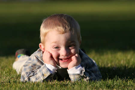 grin: cute young boy with cheeky, silly grin laying in the grass