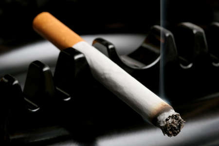 cancerous: cigarette smoking away in a black ashtray, macro with shallow dof and focus on tip