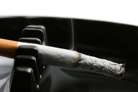 cancerous: cigarette macro, smoking in ashtray. shallow depth of field with focus on tip.