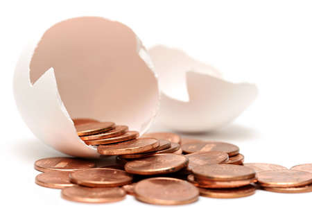 pennies: money egg - pennies pouring out of a broken egg, highkey over white with limited depth of field Stock Photo