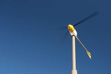 wind turbine with motion blur, against blue sky photo