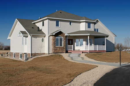 outskirts: new american home - brand new house on the outskirts of town against a blue sky