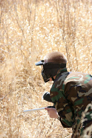 fatigues: paintball - teen paintballer with gun and fatigues on the prowl