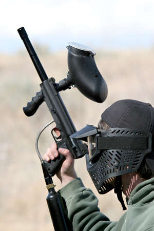 protective mask: paintball - teen paintballer with gun, wearing protective mask. focus on head.