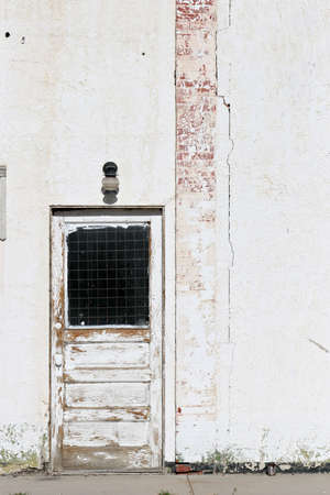 urban decay - beat up looking door in a white wall with faded paint Stock Photo - 410134