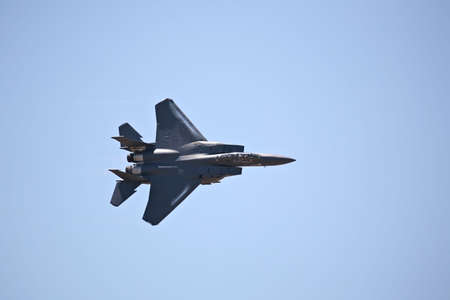 F-15 strike eagle in flight against blue sky, banking hard right photo