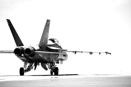 weaponry: F18 taxiing to runway for takeoff. converted to b&w with overexposed background, focus on rear of aircraft.