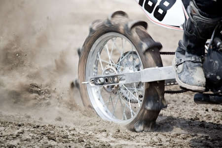 wheel of a dirtbike, paddle wheel used in hillclimbing with full motion blur. shallow depth of field, focus on center of wheel. photo