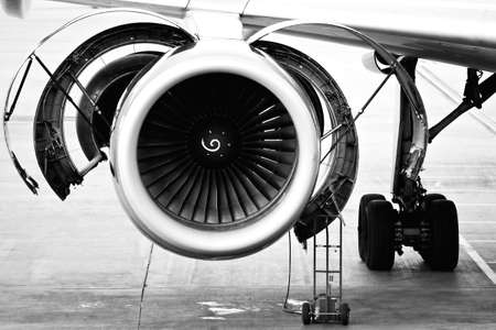aircraft engine maintenance  servicing - opened panels of a large engine of parked aircraft. highkey b&w image, slight grain. Stock Photo