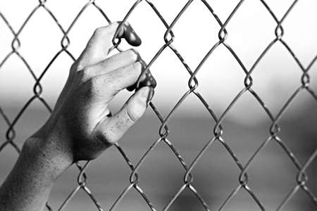chain link: depression - close up of hand on chain-link fence. Limited depth of field, converted to black and white with added grain.