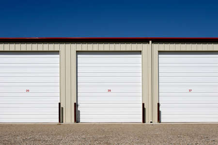 storage units, three numbered units against blue sky photo