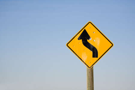 winding road sign with bullet holes - turbulent times ahead, dangerous future. photo
