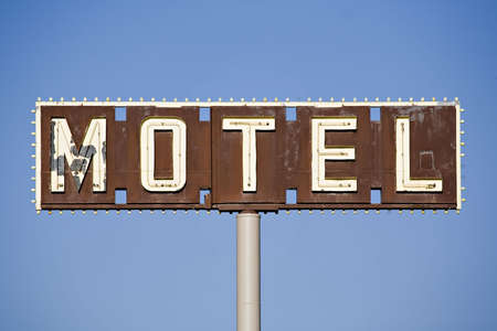 disrepair: motel sign - old sign in disrepair against blue sky Stock Photo