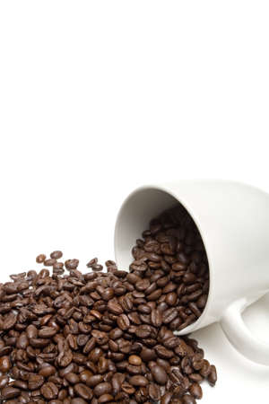 confess: spill the beans - white coffe cup with whole coffee beans spillt on white background. closeup with limited dof. Stock Photo