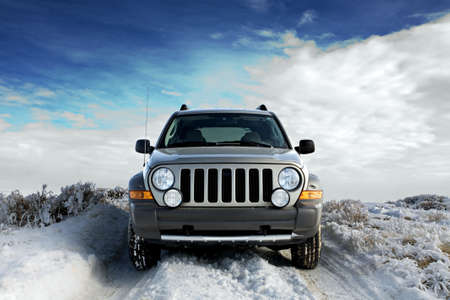 winter road: SUV on a rural snowy frosted road, winter sky background