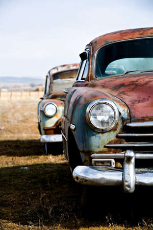 rusted: vintage car - two vintage cars abandoned on a field in rural wyoming. vertical version.