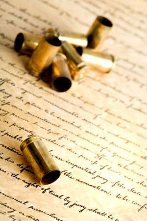 bill of rights: bullets - spent bullet cases, macro with focus on foremost shell, on bill of rights