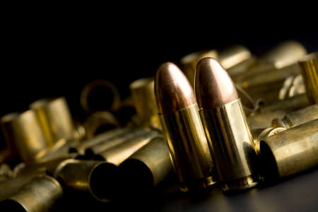 casings: bullets on black, full 9mm rounds and spent casings, macro with focus on front round