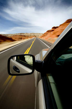 car driving through the Bighorn Canyon, Wyoming, with motion blur. SUV, focus on mirror. Stock Photo