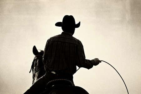 rodeo americano: vaquero en el rodeo - tirado retroiluminado contra la nube grande del polvo, convertida con el grano agregado