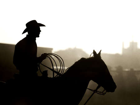 cowboy with horse and lasso, a dusty backlit silhouette. converted with added grain, shot in small town Wyoming Stock Photo