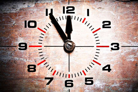 forewarning: five to twelve - old industrial clockface showing 11:55 on grunge brick background