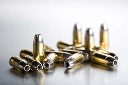 firepower: bullets 9mm shot closeup on brushed metal background, highkey with limited dof focus on two left bullets Stock Photo