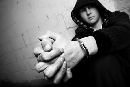 youth crime: teen in handcuffs against wall, slight added grain. focus on cuffs. Stock Photo