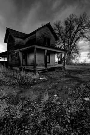 haunted house in rural Wyoming, processed HDR for dark, moody look with light added grain.  Stock Photo