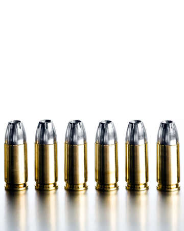 war crimes: bullets 9mm closeup on brushed metal, white background, high contrast Stock Photo