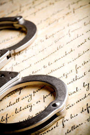 constraint: handcuffs closeup on United States Constitution with focus on Liberty Stock Photo