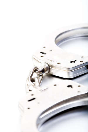 restraint device: handcuffs closeup and high key on brushed metal, focus center frame with limited dof