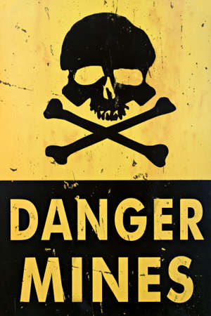 lethal: danger mines - old sign warning of land mines or minefield, closeup