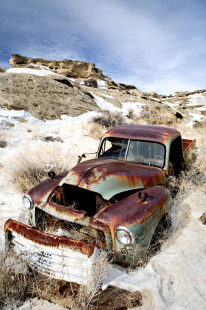 forgotten: abandoned vintage car rusting away in the snow Stock Photo